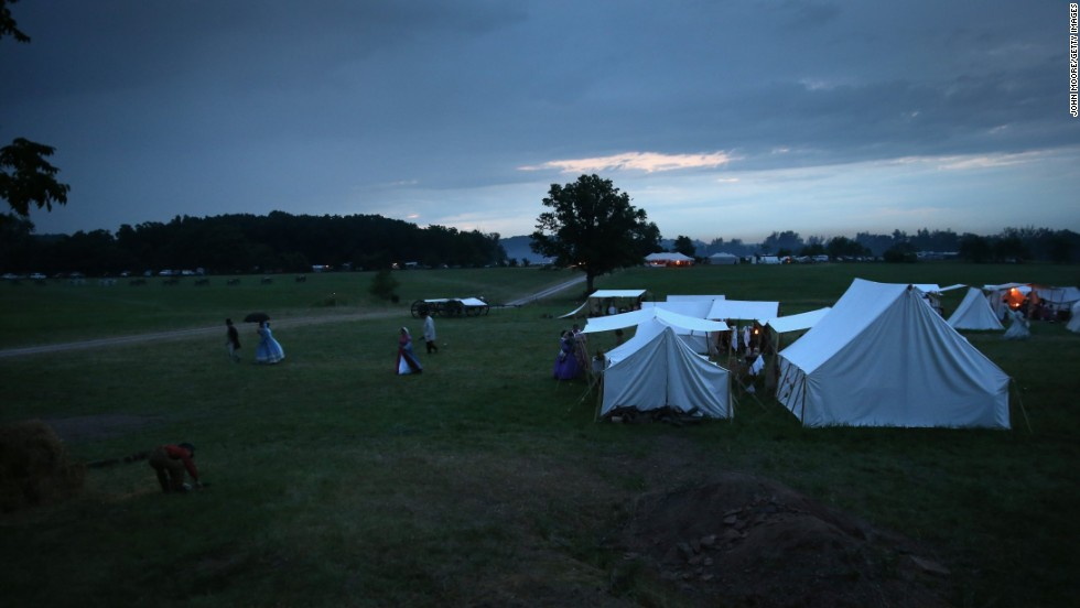 Reenactors take shelter from an evening rain storm in tents on June 29.