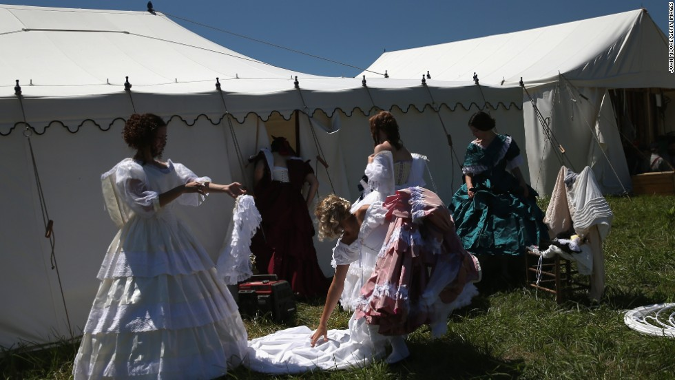 Women remove Civil War-era dresses while participating in the event on June 29.