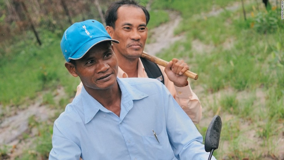 A local schoolteacher supplements his modest income by guiding intrepid travelers to remote temple ruins within the jungle that blankets Mount Kulen, much of which is riddled with landmines. In back, another tour guide wields a scythe -- essential for slashing a path through the dense vegetation.