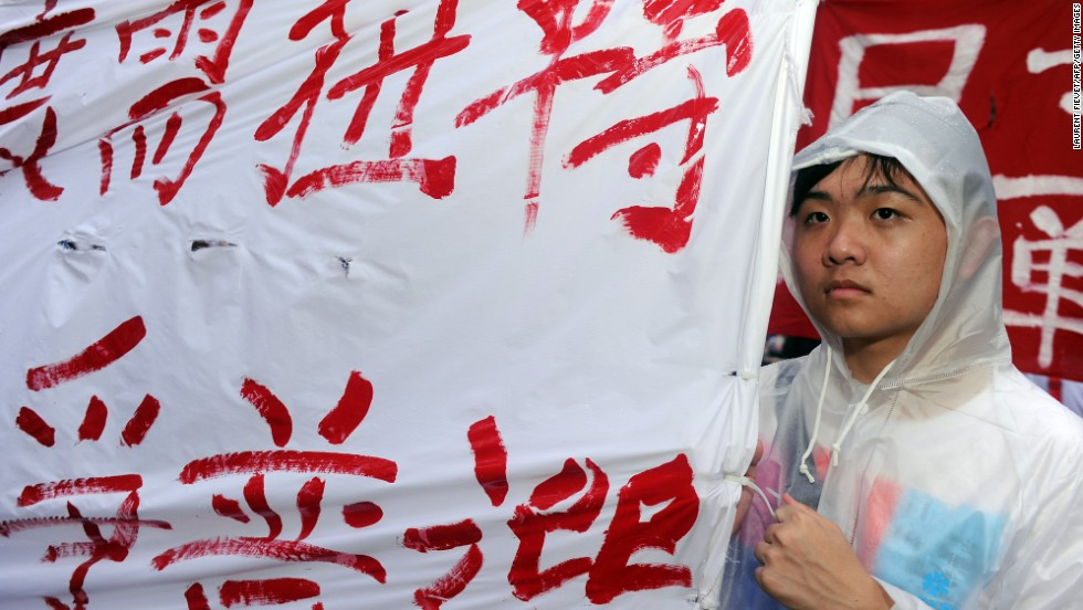 A protester holds a banner demanding universal suffrage for the special administrative region of Hong Kong, which is part of Chinese national territory while maintaining a high degree of autonomy.