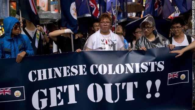 Protesters rallying for democracy on July 1, 2013 carry British-era Hong Kong flags and a banner that reads 'Chinese Colonists Get Out!!'