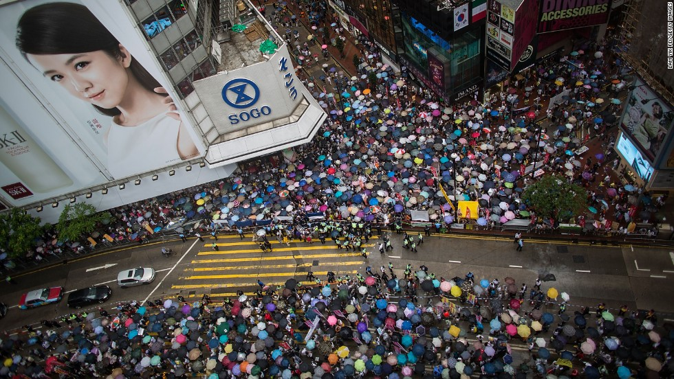 An aerial view of a sea of umbrellas marching through the shopping district of Causeway Bay.