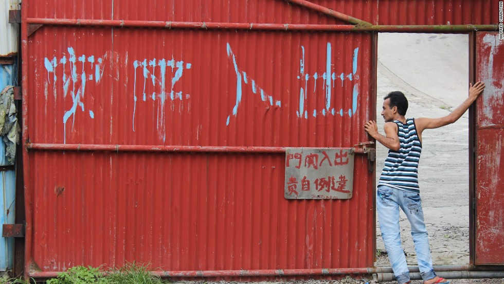 "Delwar, a refugee from Bangladesh, leans out of the main entrance of a housing compound in the slum village of Ping Che on June 25, 2013. The large Chinese characters read, ""Peace and safety to those who enter and leave."""