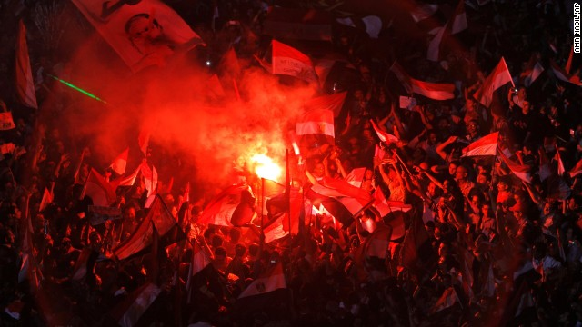 Opposition protesters celebrate on July 3, lighting flares and waving national flags in Tahrir Square.