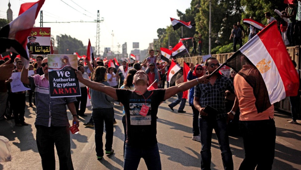 Opponents of Morsy wave national flags during a protest outside the presidential palace in Cairo on July 3.