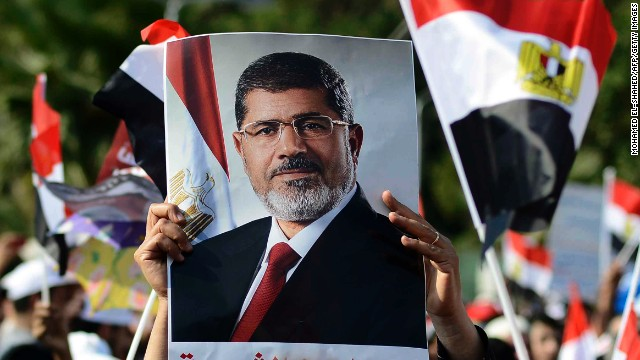 A supporter of Islamist Egyptian President Mohamed Morsi holds up his image during a rally outside Cairo University on June 2, 2013. A top Muslim Brotherhood leader urged Egyptians to stand ready to sacrifice their lives to prevent a coup, after the army gave Islamist President Mohamed Morsi and his opponents until July 3 to resolve their differences or face intervention.