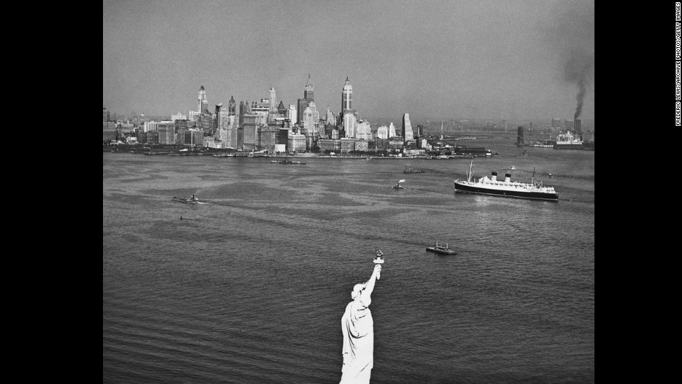 The towering skyline of downtown Manhattan is seen behind the statue in 1950.