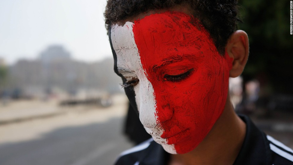 A boy with face paint the color of the Egyptian flag pauses on July 4 in Tahrir Square.