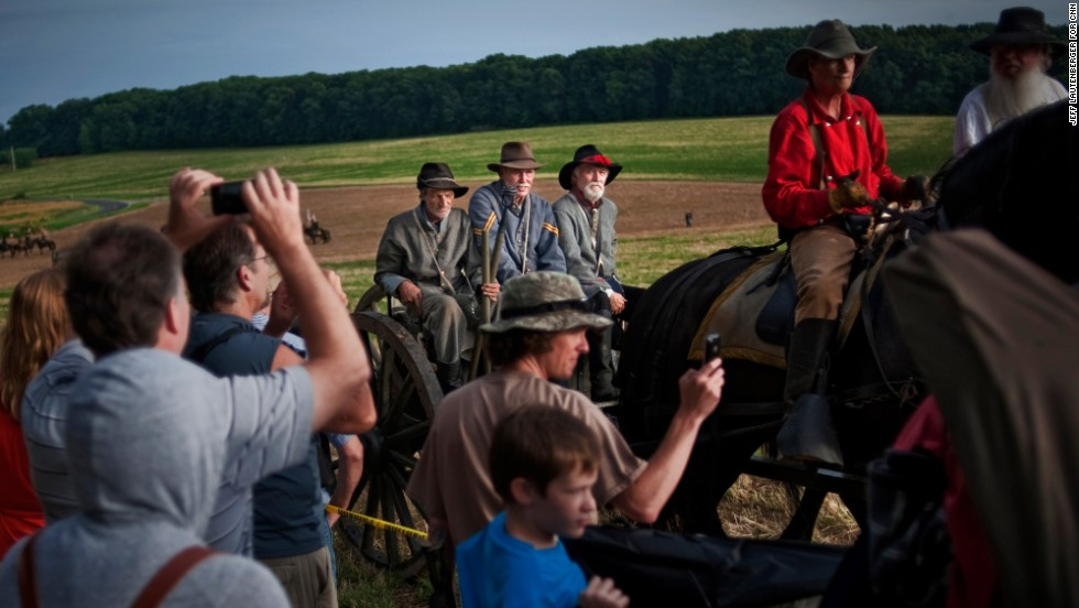 Spectators vie for position on July 2, to get a good photo of a carriage of Confederate re-enactors leaving the scene of a battle.