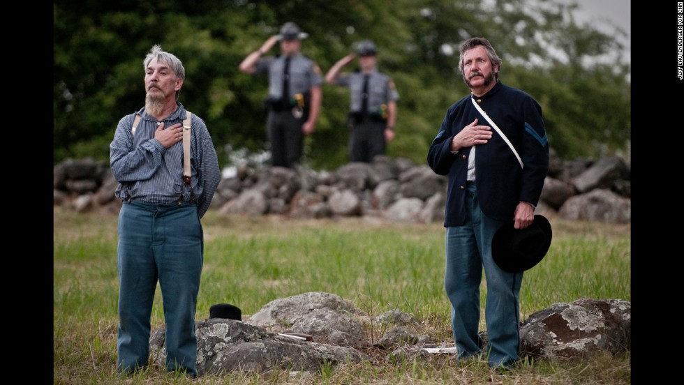 "Union re-enactors Jed LaBounty, left, and Eugene Lisewski stand in front of two National Park Service rangers on June 30, as country singer Trace Adkins performs the national anthem during the NPS commemoration of the Battle of Gettysburg, titled ""A New Birth of Freedom."""