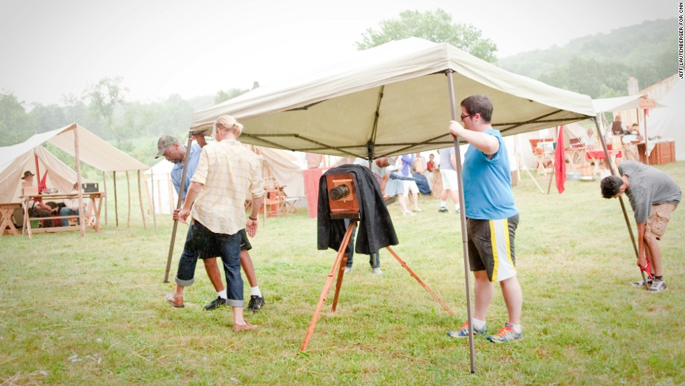 Production assistants rush to cover an original tintype camera and lens with a modern collapsible tent in a field of Civil War-era tents, as a sudden rainstorm pops up on June 28, during the re-enactment of the Battle of Gettysburg.