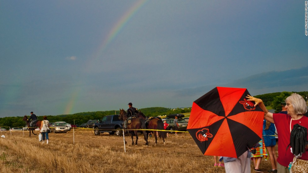 A rainbow rises over the parking lot on July 2, at Sheppard Farm near Hanover, Pennsylvania, as Union horsemen return to their campsite and spectators leave the re-enactment.