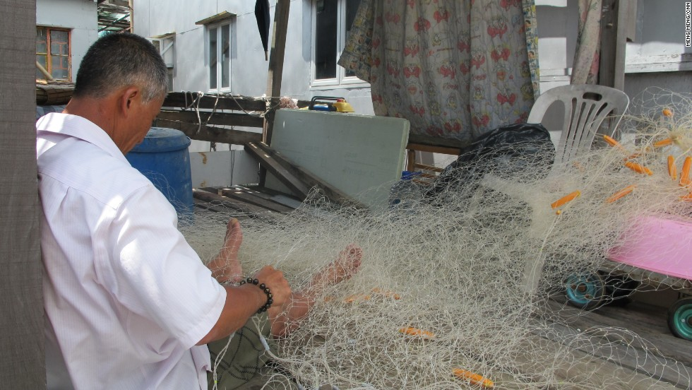 A local fisherman uses home-knitted nets after the government banned trawling.