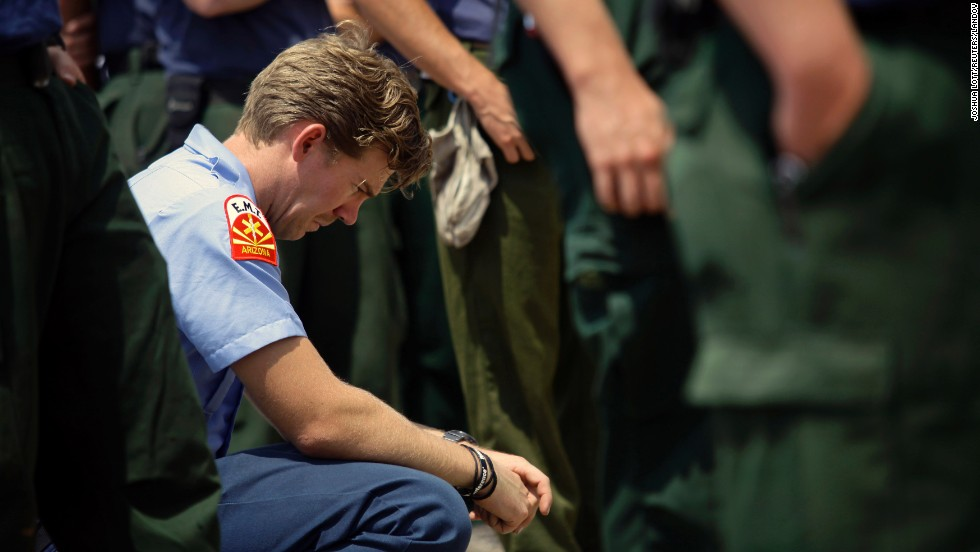Firefighter Sean Kauffman pays his respects at a makeshift memorial outside the Granite Mountain Interagency Hotshot Crew fire station in Prescott, Arizona, on Thursday, July 4. Kauffman is a former member of the elite firefighting crew.