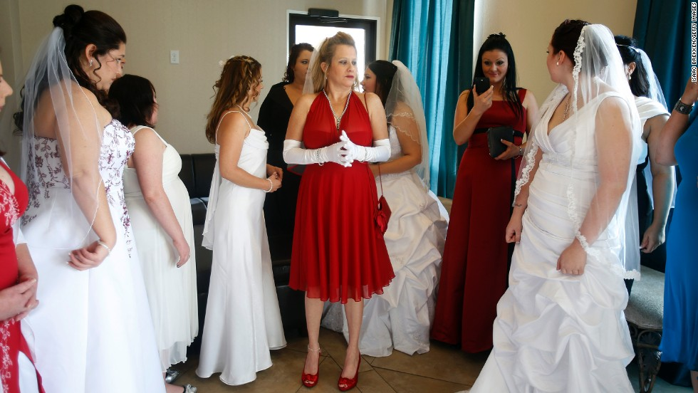 A dozen brides wait to be married during a ceremony for a radio station contest at the Little Chapel of the Flowers on December 12, 2012, in Las Vegas.