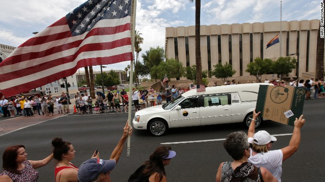 A procession of 19 hearses for the hotshot firefighters goes through Phoenix on Sunday.