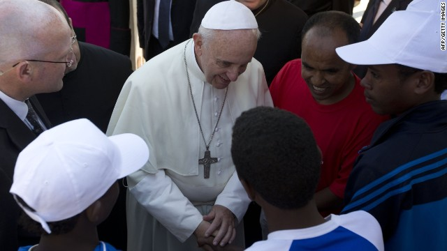 Pope Francis (C) greets migrants during his visit to the island of Lampedusa, a key destination of tens of thousands of would-be immigrants from Africa, during his visit on July 8, 2013