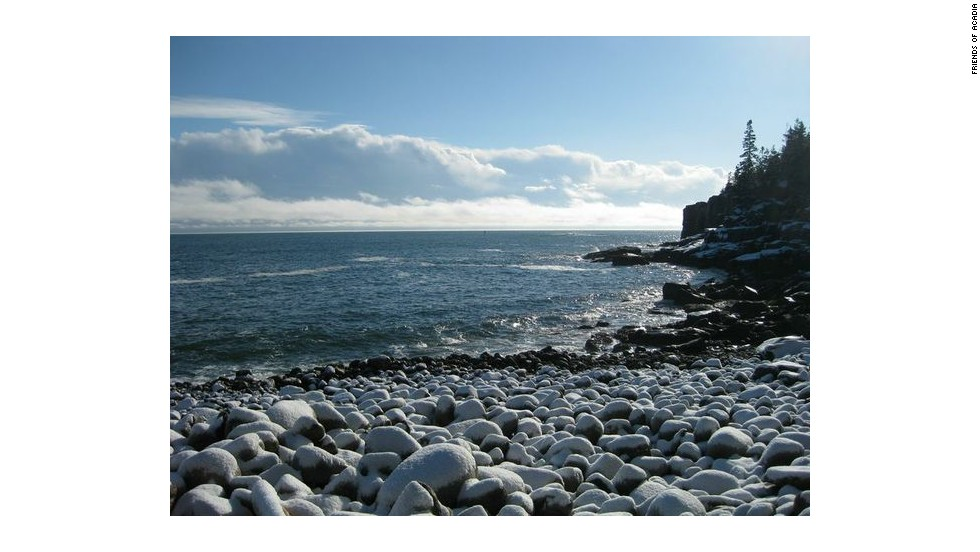 Otter Cliffs, noted for world-class rock climbing, overlooks a beach covered in cobblestones.