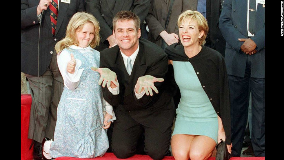 Carrey, with his daughter Jane and then-girlfriend Lauren Holly, shows his cement-covered hands during his hand and foot print ceremony outside the famous TCL's Chinese Theatre in Hollywood, California, in 1995.
