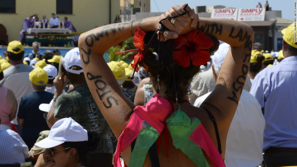 """A faithful has """"Stop clowning with Lampedusa"""" painted on her arms as the pope led  the mass. """"The culture of well-being, that makes us think of ourselves, that makes us insensitive to the cries of others, that makes us live in soap bubbles, that are beautiful but are nothing, are illusions of futility, of the transient, that brings indifference to others, that brings even the globalization of indifference,"""" said Pope Francis. <br />"""