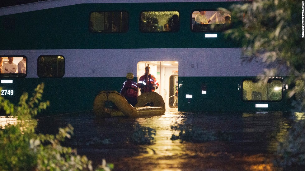 Rescue workers bring a dingy over to a Go Train stuck in floodwaters on July 8. Evacuations of passengers lasted until early Tuesday, July 9.
