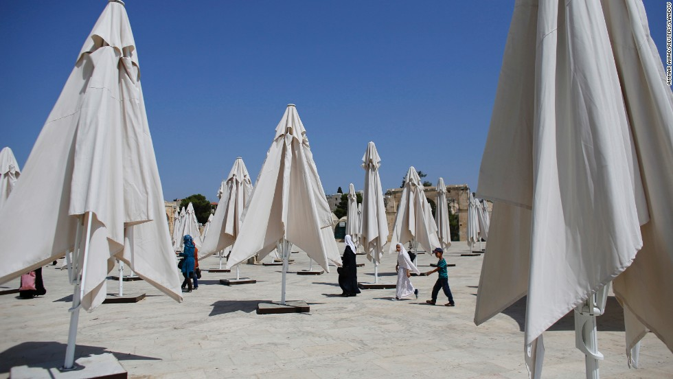 People walk past parasols in Jerusalem on July 8.