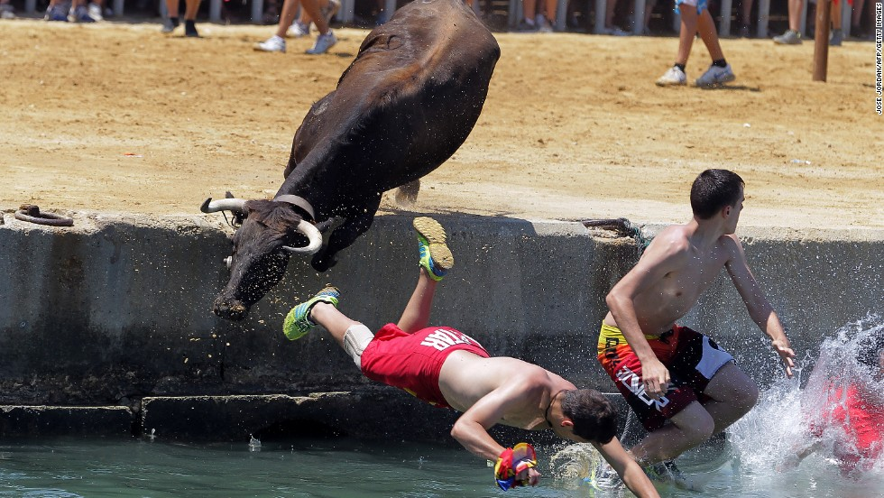 "People leap into the water during the traditional ""bous a la mar,"" or bull in the sea, event at Denia harbor near Alicante on July 8."