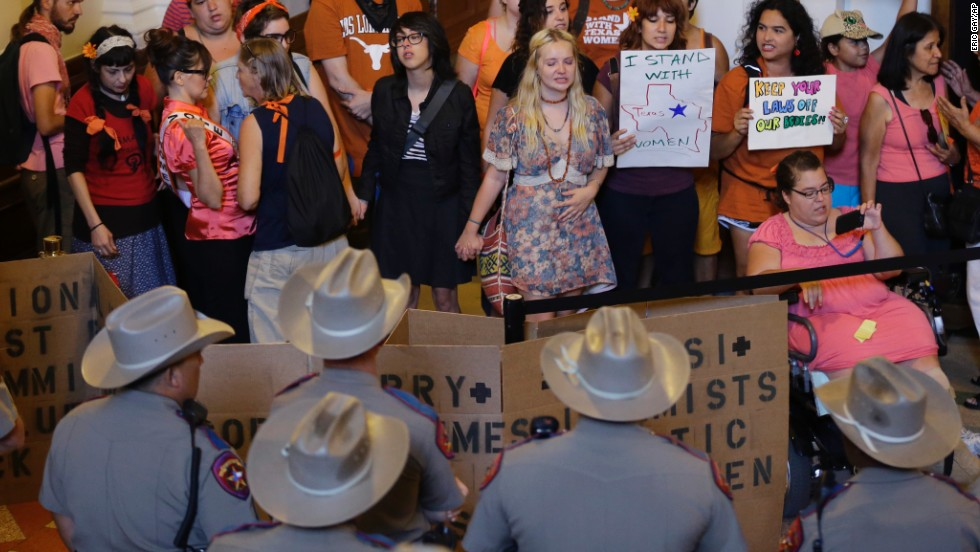 State troopers look on as a group in Austin, Texas, protests a new state abortion law in July. Parts of the law were ruled unconstitutional on Monday, October 28 -- a day before they were scheduled to take effect.