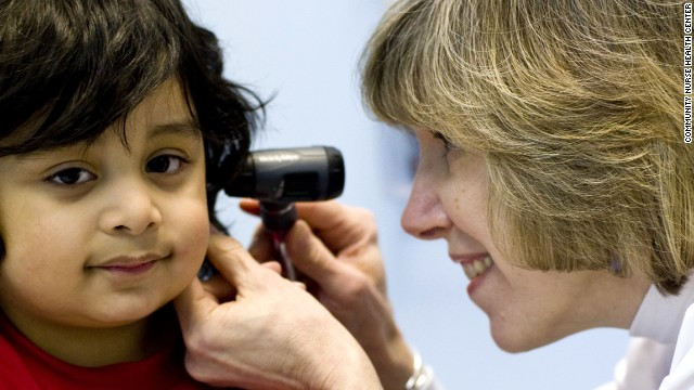 A Community Nurse Health Center doctor in La Grange, Illinois, examines a young patient.