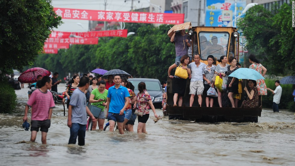 Residents travel on an excavator through flooded streets in Chengdu, the capital of Sichaun province, on July 9.