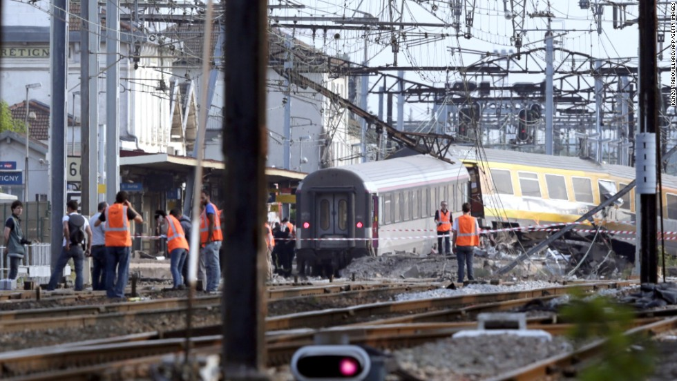 Rescuers work on the site of a train accident in the railway station of Bretigny-sur-Orge, on Friday, July 12 near Paris. The train was passing through the station but was not scheduled to stop there, according to Guillaume Pepy, president of the French national railway company, SNCF.
