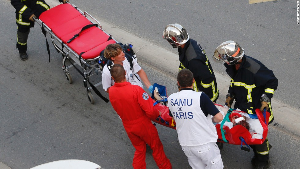 Emergency crews help transport a victim from the scene of the accident on July 12.