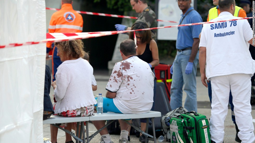 People injured in the accident wait for medical assistance on July 12, near the scene of the accident.