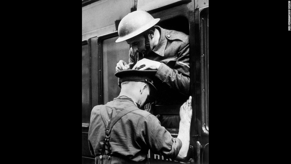 A soldier uses a comrade's hat to lean on as he writes a telegram home circa 1940.