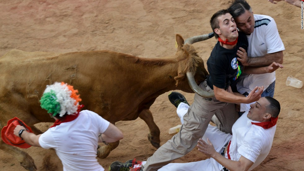 People are pushed by a bull in the bull ring in Pamplona on July 14.