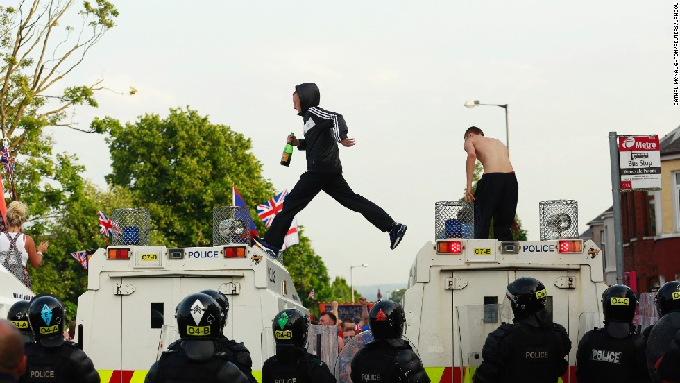 Protesters climb onto police vehicles in the Woodvale Road area of Belfast on July 12.