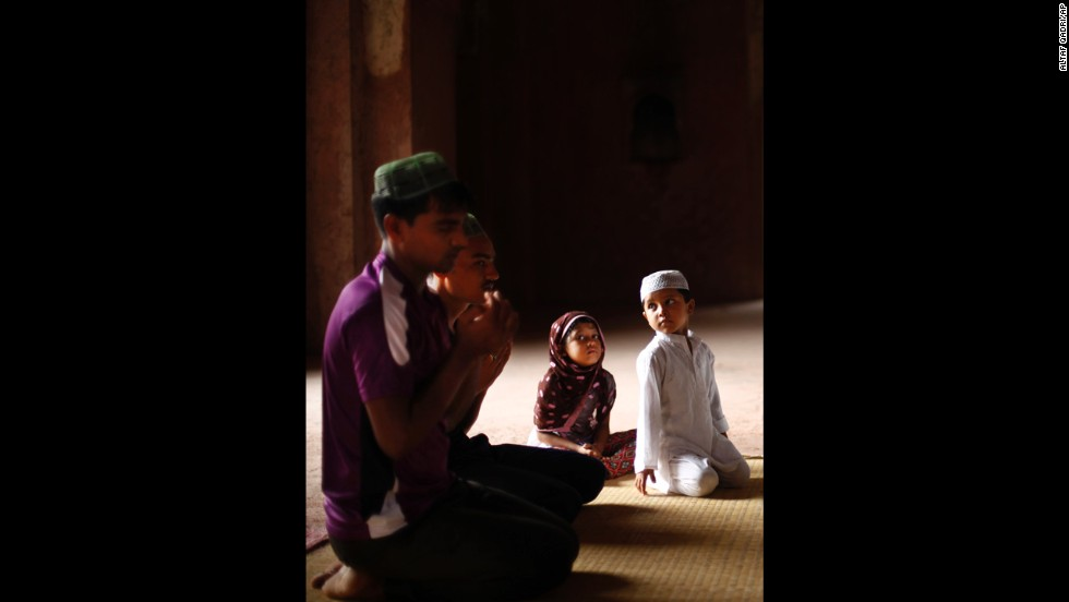 Children watch as adults pray at a mosque in New Delhi on July 12, the first Friday of Ramadan.