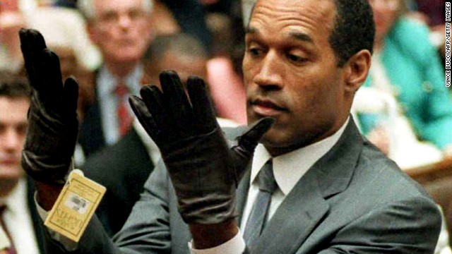 O.J. Simpson looks at a new pair of Aris extra-large gloves that prosecutors had him put on 21 June 1995 during his double-murder trial in Los Angeles. Simpson was acquitted of charges of murdering his ex-wife Nicole Simpson and her friend Ronald Goldman.  AFP PHOTO by Vince BUCCI (Photo credit should read Vince Bucci/AFP/Getty Images)