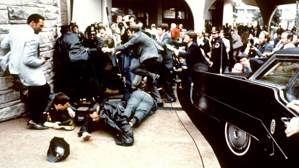 As the bullet hits Reagan, lead agent Jerry Parr grabs the president's shoulders and pushes him down into the limo.  Secret Service agent Ray Shaddick slams the door shut and the motorcade bolts from the scene.