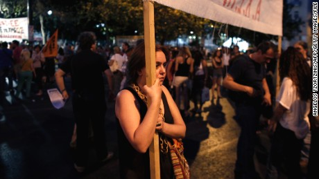 A protester, holding a banner against the Greek government, takes part in a demonstration in July 2013 in Athens.