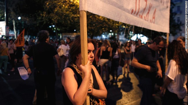 A protestor holding a banner against the Greek Government takes part in a demonstration on July 15, 2013 in Athens.