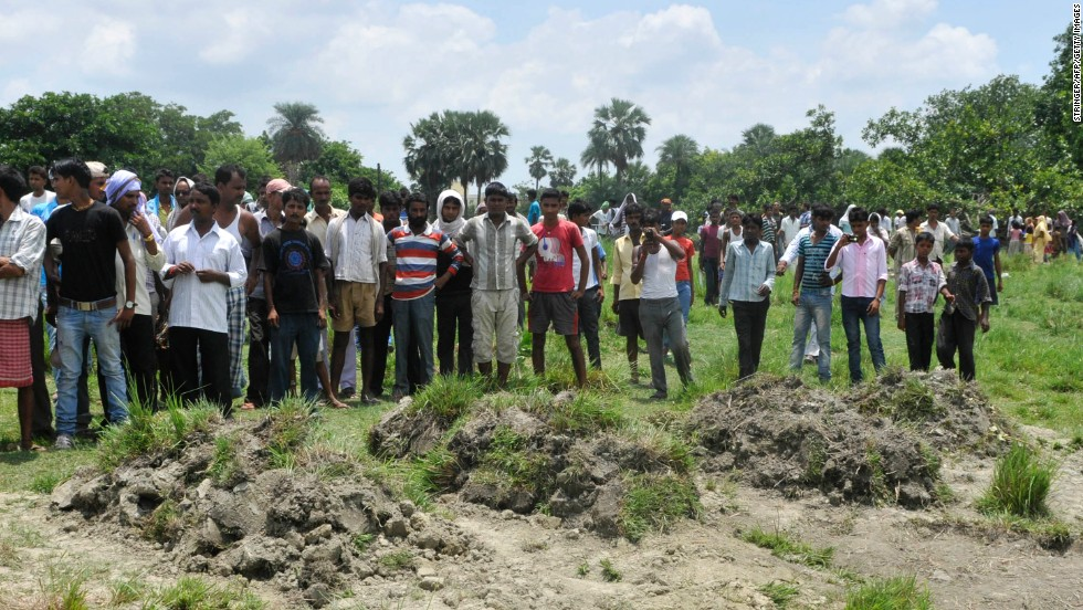 Villagers gather for a funeral for children who died from the poison.