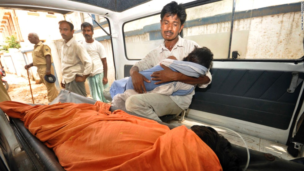 An Indian man mourns as he holds his dead daughter inside an ambulance, outside a hospital in Patna.