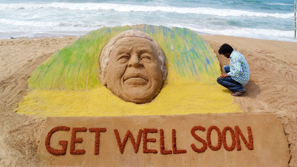 <strong>INDIA: </strong>Artist Sudarshan Pattnaik works on a sand sculpture in Puri to wish Mandela a speedy recovery. The former South African president was in critical but stable condition at the time, according to officials.