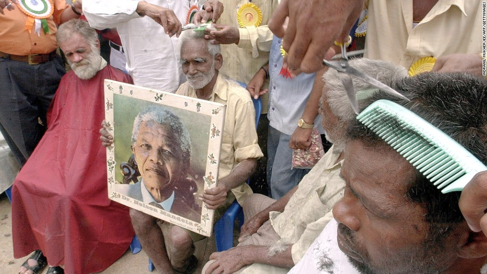 <strong>INDIA:</strong> An elderly man in Bangalore holds a portrait of Mandela as he receives a free haircut to commemorate the 84th birthday of the former South African president in 2002.