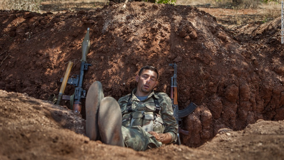 A rebel fighter naps in a trench about 300 feet from the Syrian government forces' positions along the highway connecting Idlib with Latakia on Monday, July 15.