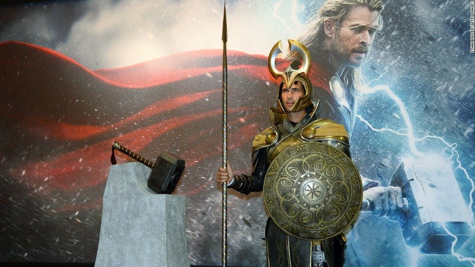 "A person dressed as a character from ""Thor: The Dark World"" stands guard in front of a display for the movie."