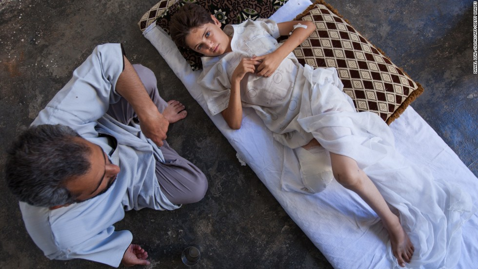Yahya Sweed, 13, is comforted by his father as he lies on a bed in Kfar Nubul on Tuesday, July 16. The boy was injured by shrapnel, resulting in the amputation of his right leg.