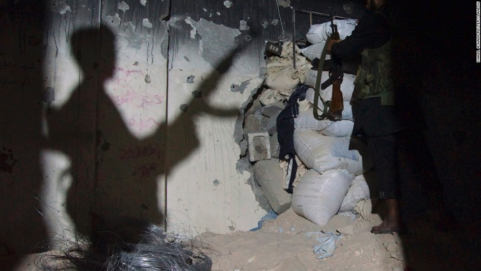 A Free Syrian Army fighter casts a shadow on a wall as he carries his weapon in a shelter in Deir al-Zor on Thursday, July 18.