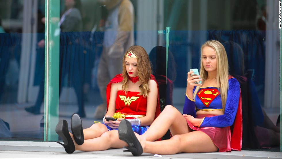 Joy Donaldson, left, dressed as Wonder Woman, and Everleigh Reed as Supergirl, take a break outside of the convention on July 20.